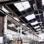 Een lichtverhitter van Schwank onder het plafond van een industriegebouw.