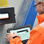Iemand bedient de SchwankControl Touch-regeling voor verwarmingssystemen van Schwank.